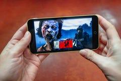 Berdyansk Ukraina - mars 17, 2019: Händer som rymmer en smartphone med in i den döda leken för 2 mobil på skärmskärmen som är red arkivfoto
