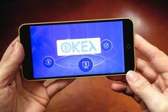 Berdyansk Ukraina - mars 17, 2019: OKEx logo som visas på en modern smartphone arkivbild