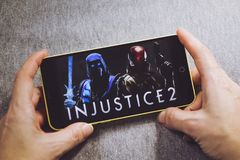 Berdyansk Ukraina, Marzec, - 4, 2019: Ręki trzyma smartphone z niesprawiedliwości 2 grze na pokazu ekranie obrazy royalty free