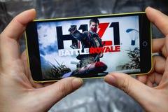Berdyansk Ukraina, Marzec, - 18, 2019: Zbliżenie telefonu ekran z H1Z1 battle royale Mobilną grze bawić się na Smartphone zdjęcia stock