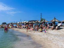 Berdyansk, Ukraine June 30, 2018: beach resort seasonon the coast of the Azov Sea. People are sunbathing on the beach. Berdyansk, Ukraine June 30, 2018: The stock photo