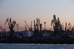 BERDYANSK - UKRAINE, LE 2 SEPTEMBRE 2016 : Silhouette de beaucoup grande de grues dans le port maritime Images libres de droits