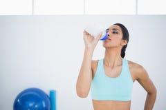 Bere d'uso degli abiti sportivi della donna sportiva adorabile della bottiglia di sport Fotografie Stock