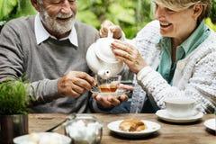 Bere senior del tè di pomeriggio delle coppie si rilassa il concetto immagine stock