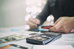 Berechnen Sie auf Schreibtisch mit dem Geschäftsmann, der Finanzierung tut Stockbilder