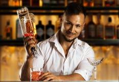 Bereidt de Insanely sexy jonge mens gemengde dranken voor zijn gasten voor Royalty-vrije Stock Fotografie