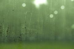 Bereift glassed mit Wassertropfen und grünem Garten hinten Stockfotografie