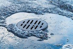 Bereifte Pfütze mit rundem Abwasserkanaleinsteigeloch Stockfoto