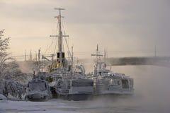 Bereifte Schiffe und Fluss in einem eisigen Nebel stockbild