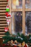 Bereiftes Fenster mit Feiertagsdekorationen Stockfotografie