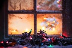 Bereiftes Fenster mit festlichen Leuchten Stockfotografie