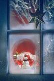 Bereiftes Fenster mit Weihnachtsdekorationen nach innen Lizenzfreies Stockbild
