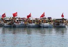 Bereisen Sie Boote mit den türkischen Flaggen, die auf Touristen an Iztuzu-Strand warten Stockbilder