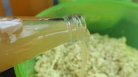 Bereiten Sie ältere Beerenköpfchen zur Herstellung des Staus von ihm vor füllende Flasche Apfelsaft in der Schüssel stock video footage