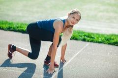 Bereiten Sie vor, um zu gehen! Weiblicher Athlet auf der Anfangszeile einer Stadionsbahn, die Kamera betrachtet und, bereitend fü Stockfoto