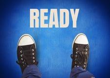 Bereiter Text und schwarze Schuhe auf Füßen mit blauem Hintergrund Stockfotografie