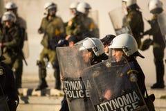 Bereitschaftspolizei mit ihrem Schild, gehen während einer Sammlung vor Athen-Universität in Deckung Stockbild