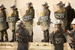 Bereitschaftspolizei mit ihrem Schild, gehen während einer Sammlung vor Athen-Universität in Deckung Lizenzfreies Stockbild