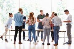 Bereitstehende Schreibtische Lehrer-With College Studentss im Klassenzimmer Lizenzfreies Stockbild