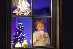 Bereitstehendes Fenster des kleinen Jungen zur Weihnachtszeit Lizenzfreies Stockbild