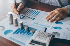 Berekenen het tellende geld van de zakenmanaccountant en het maken van nota's bij rapport die financi?n doen en over investerings stock foto