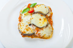 Berenjena cocida con queso, tomates y especias en una placa blanca Un plato de la berenjena está en una tabla de madera Fotos de archivo libres de regalías