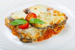 Berenjena cocida con queso, tomates y especias en una placa blanca Un plato de la berenjena está en una tabla de madera Fotos de archivo