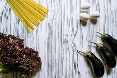 Berenjena, espaguetis y lechuga en el fondo blanco fotos de archivo
