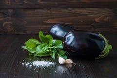 Berenjena púrpura (berenjena) con albahaca y ajo en la tabla de madera oscura Verduras crudas frescas de la granja - cosecha fran Fotos de archivo libres de regalías