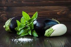 Berenjena púrpura y blanca (berenjena) con albahaca en la tabla de madera oscura Las verduras crudas frescas de la granja - cosec Imágenes de archivo libres de regalías