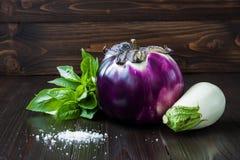 Berenjena púrpura y blanca (berenjena) con albahaca en la tabla de madera oscura Las verduras crudas frescas de la granja - cosec Fotos de archivo