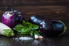 Berenjena púrpura y blanca (berenjena) con albahaca en la tabla de madera oscura Las verduras crudas frescas de la granja - cosec Fotografía de archivo