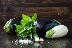 Berenjena púrpura y blanca (berenjena) con albahaca y ajo en la tabla de madera oscura Verduras crudas frescas de la granja - cos Foto de archivo libre de regalías