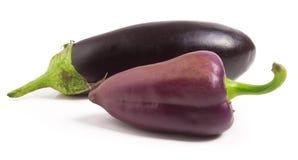 Berenjena y paprikas púrpuras aislados en el fondo blanco Imagen de archivo