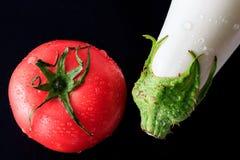Berenjena y tomate blancos en fondo negro imágenes de archivo libres de regalías