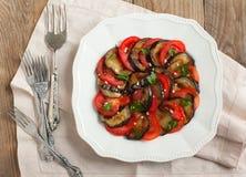 Berenjenas asadas a la parrilla con los tomates y el ajo frescos imagenes de archivo