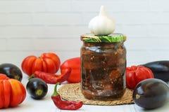 Berenjenas en la salsa aguda de la pimienta, de tomates y del ajo en tarro en la tabla fotografía de archivo libre de regalías