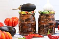 Berenjenas en la salsa aguda de la pimienta, de tomates y del ajo en tarros en la tabla foto de archivo libre de regalías
