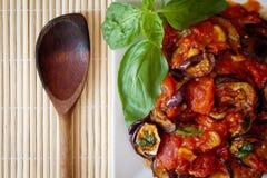 Berenjenas en salsa de tomate con la cuchara de madera imagenes de archivo