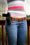 Holstered Sidearm on Ladies Belt. A Beretta Px4 Storm pistol in a holster worn by a woman on her belt. Usually intended for personal protection or by law Royalty Free Stock Photo