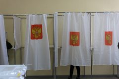 Berezniki, Россия 18-ое марта 2018: избиратель кладет пулю в урну для избирательных бюллетеней в президентских выборах стоковое фото rf