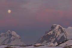 Berg av den antarktiska halvön i den röda solnedgången i moen Arkivbild
