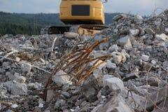 Berg av skräp med den gula grävskopan Royaltyfri Bild
