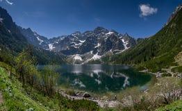 Berg avspeglar i klart vatten av en bergsjö Arkivfoton