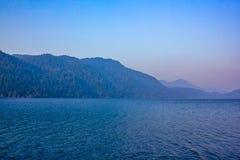 Berg bak sjön på afton i sommar med solnedgångfärger arkivfoton