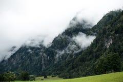 Berg-coverd in den Wolken stockfotografie