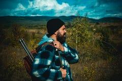 Berg de jacht Jager met jachtgeweerkanon op jacht Gebaard de holdingskanon van de jagersmens en het lopen in bos stock foto