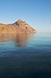 Berg, der im Meer sich reflektiert Stockfotos