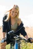Berg, der sportive sonnige Wiesen der jungen Frau radfährt Lizenzfreies Stockfoto