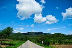 Berg, die Himmelwolken und die Straße Stockbild